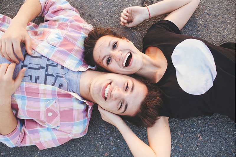 Young couple laying on their backs on pavement looking up at camera with smiles.